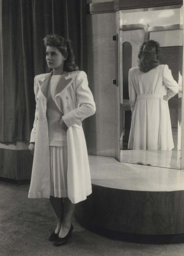 a film still of women wearing a white suit and skirt