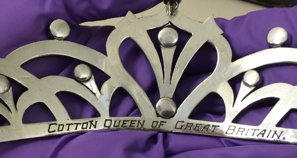 a detail of a silver tiara engraved with the words cotton queen of Great Britain