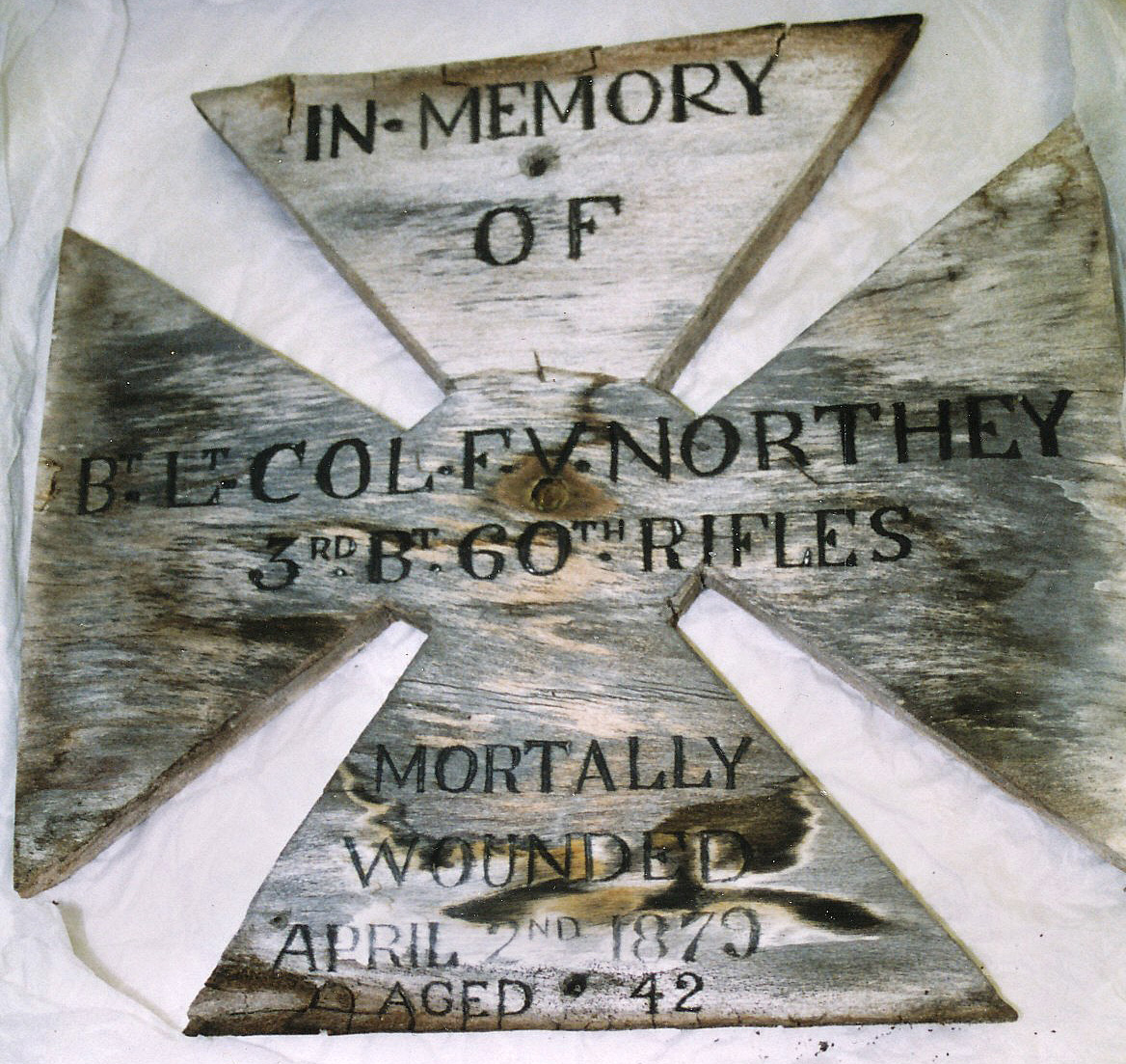 a photo of a wooden cross with the name of soldier in memory of