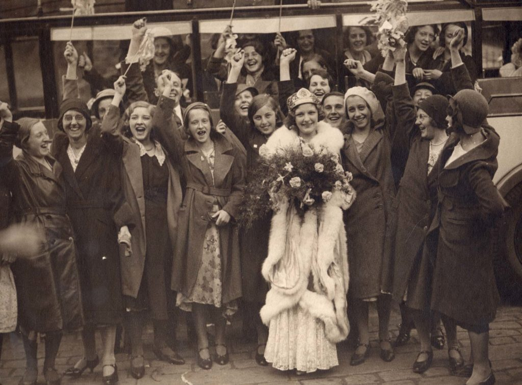 A black and white photo of a woman wearing tiara surrounded by cheering women
