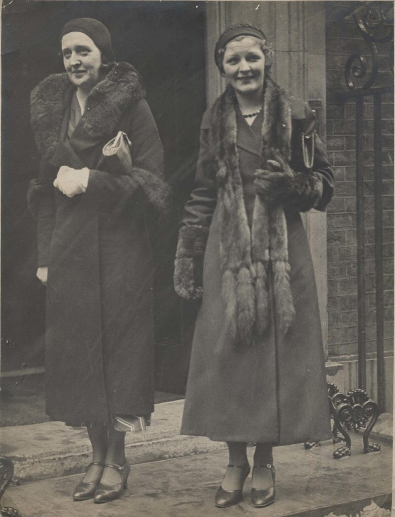 a photo of two women in long coats with fur collars outside downing street