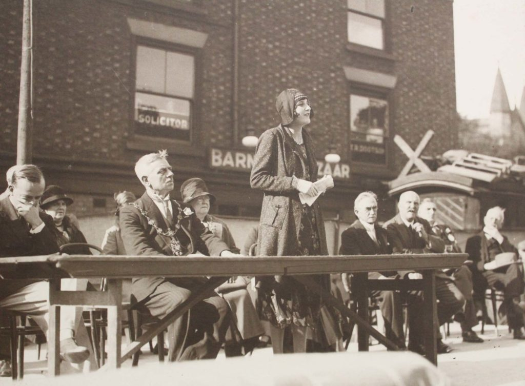 a black and white photo of a woman in 1930s dres delivering a speech on a stage outside