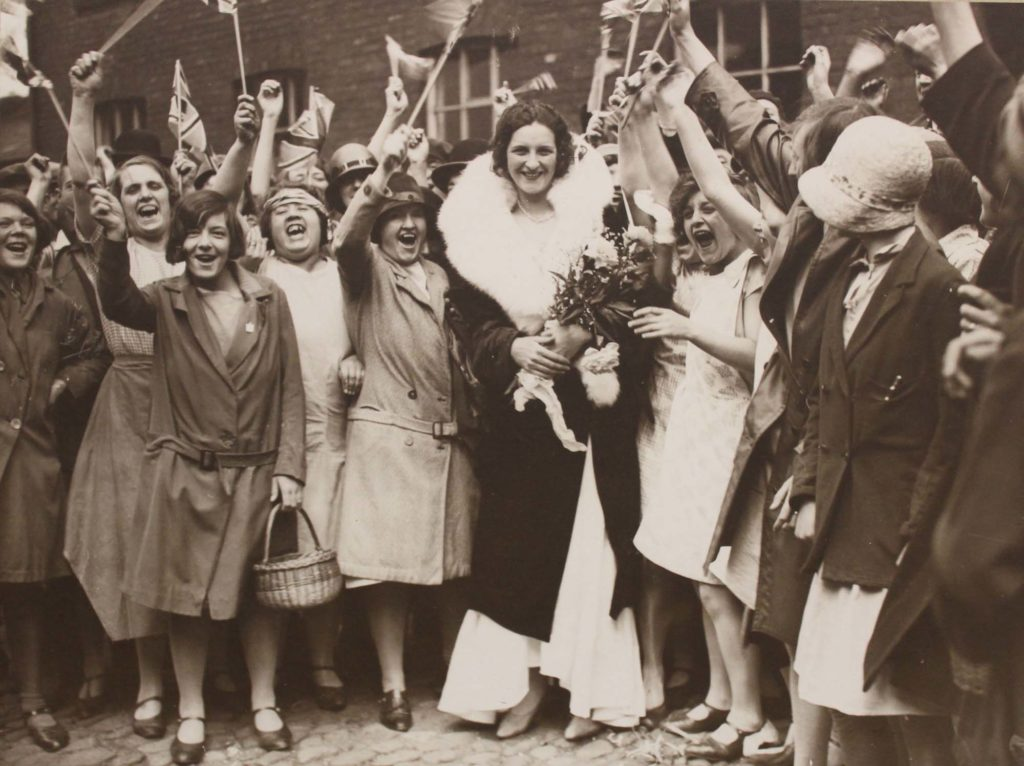 a photo of a woman in long dress surrounded by cheering female mill workers
