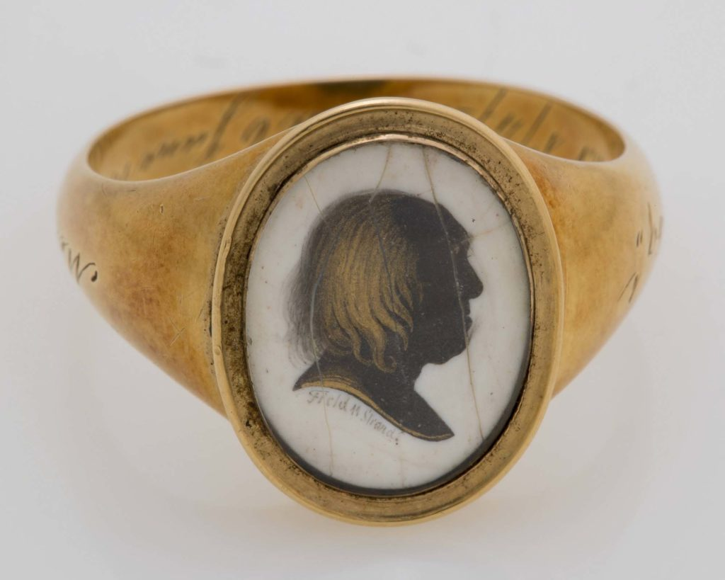 a photo of a gold ring with inlaid portrait with silhouette
