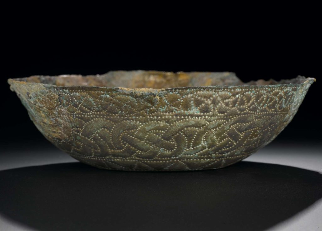 a photo of a bowl with verdigris and engraving