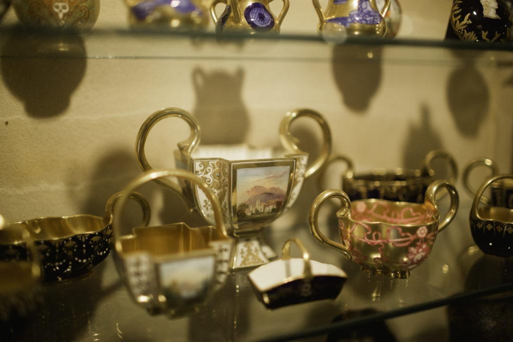 photograph of museum cabinet containing gilded ceramics