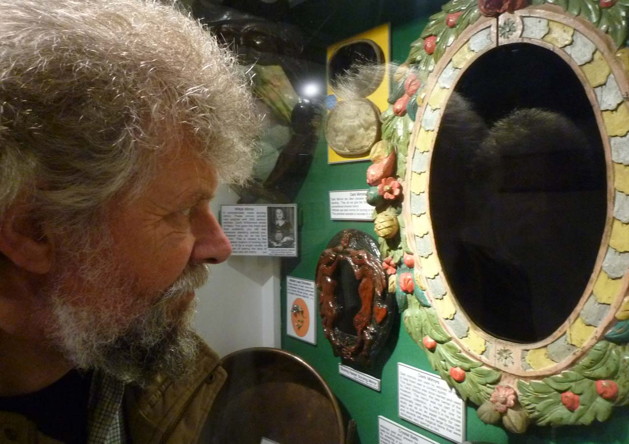 a photo of a man peering into a dark mirror with a decorated floral surround