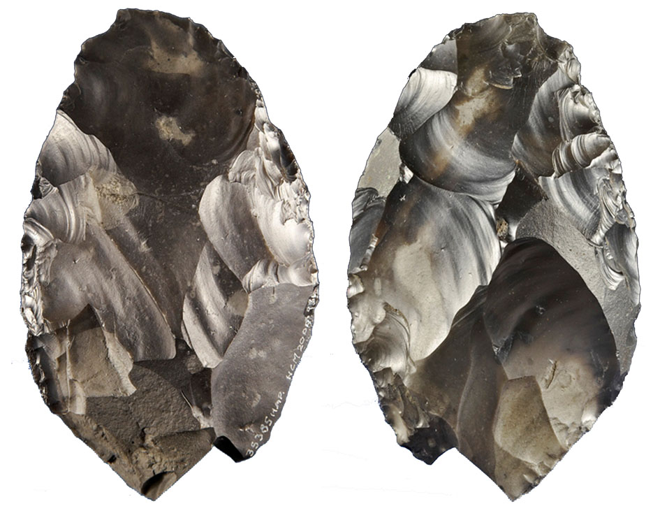 a photo showing both sides of a carved handaxe
