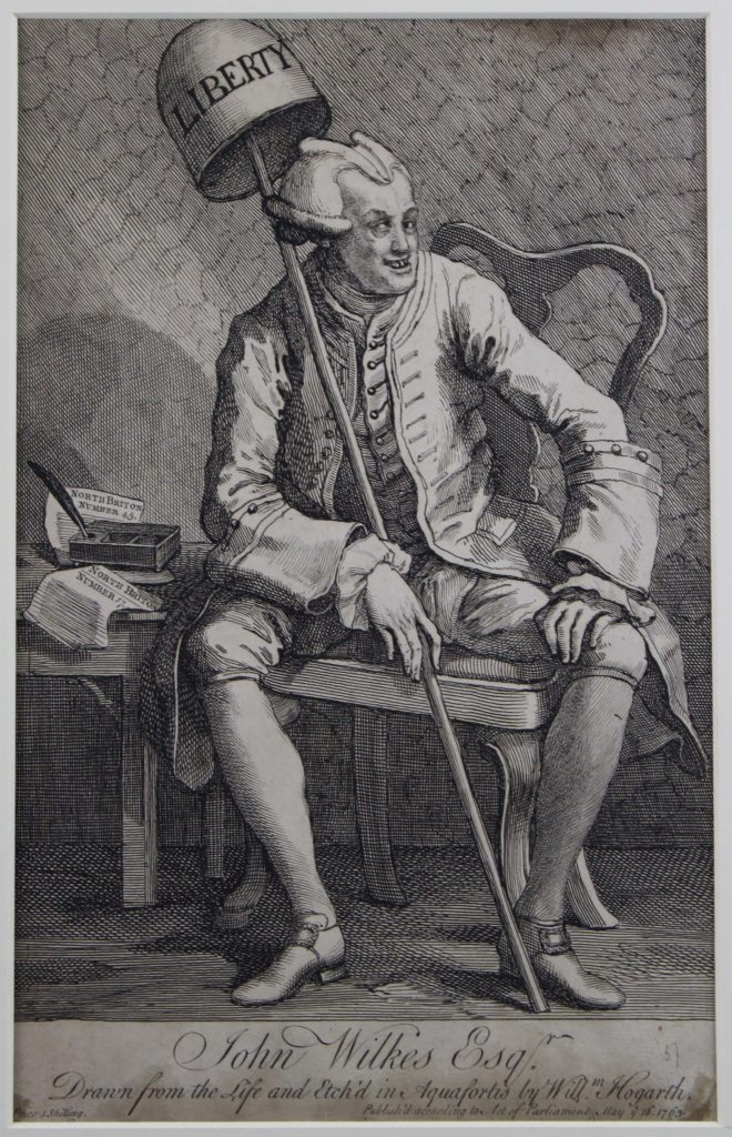 an etching of man sat on a chair with a libery cap and horns protruding from his Georgian style wig