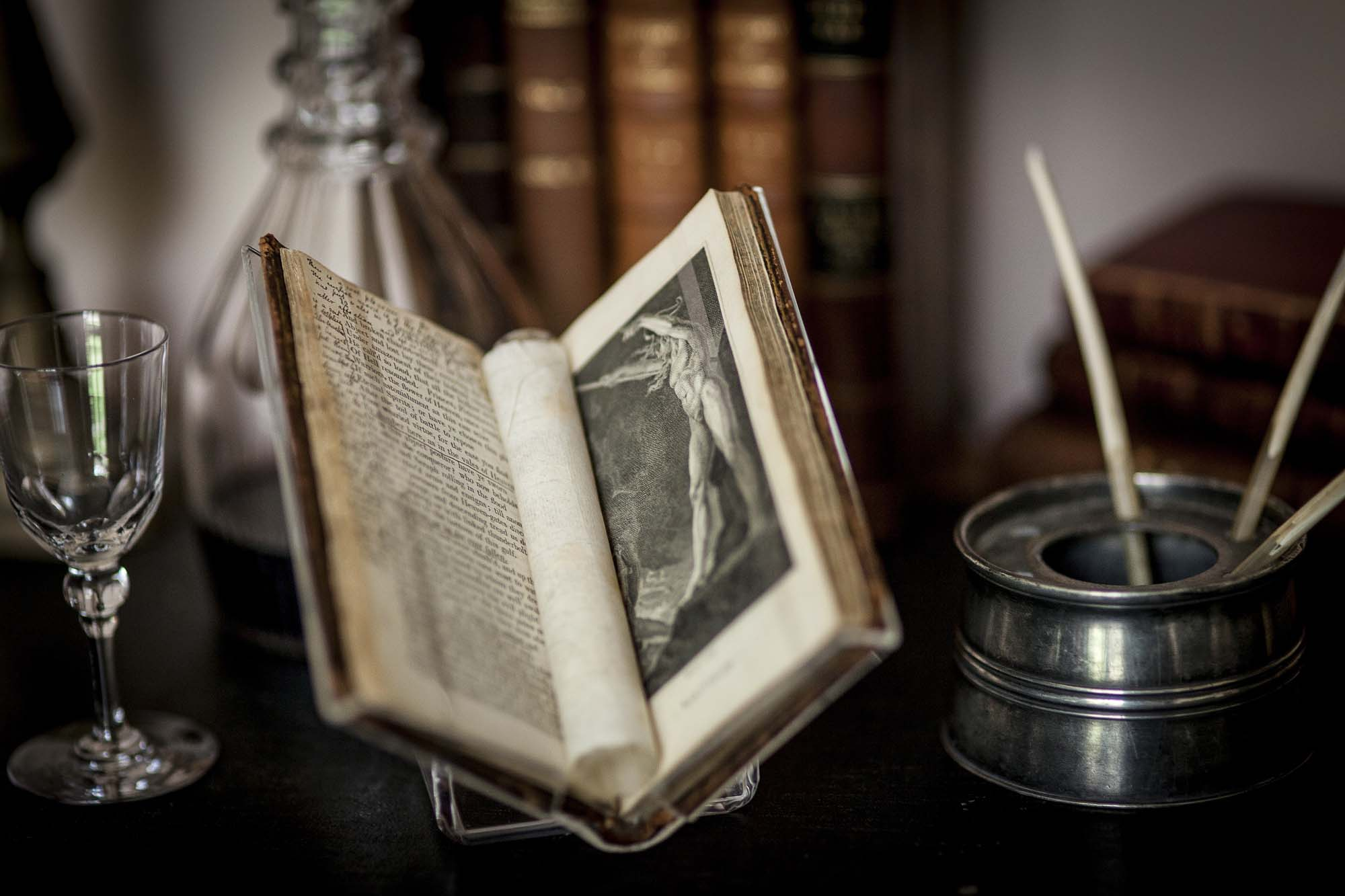 a photo of an open book on desk with pewter ink pot and port decanter