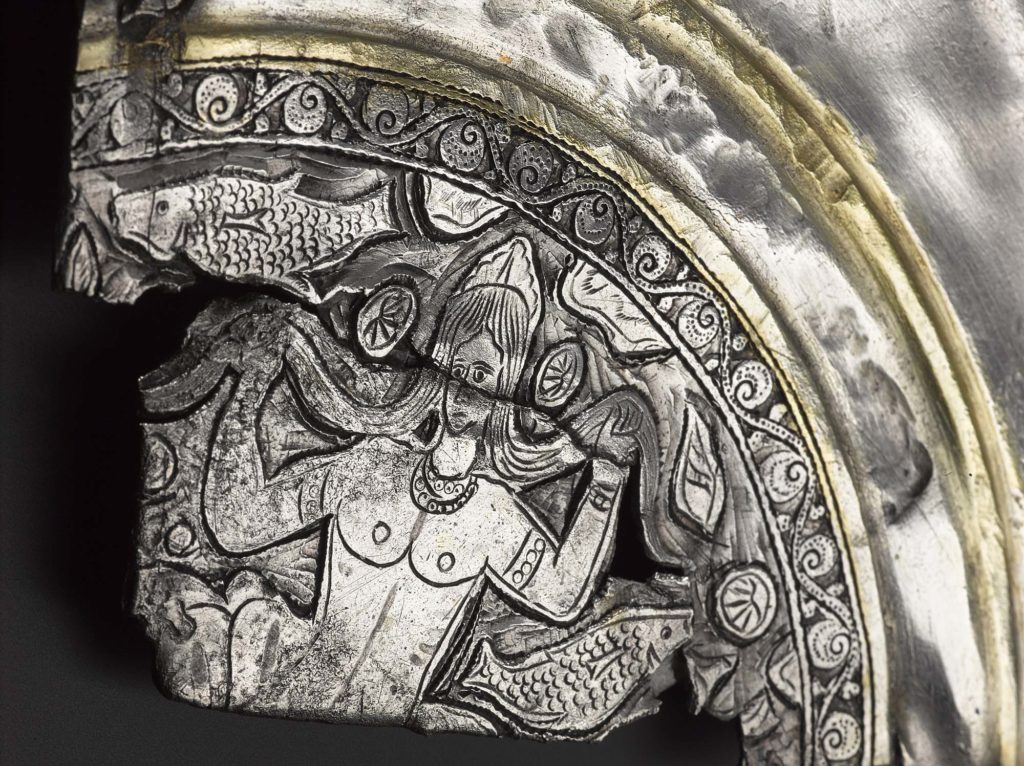 a photo of a fragment of an engraved plate with a naked woman on it