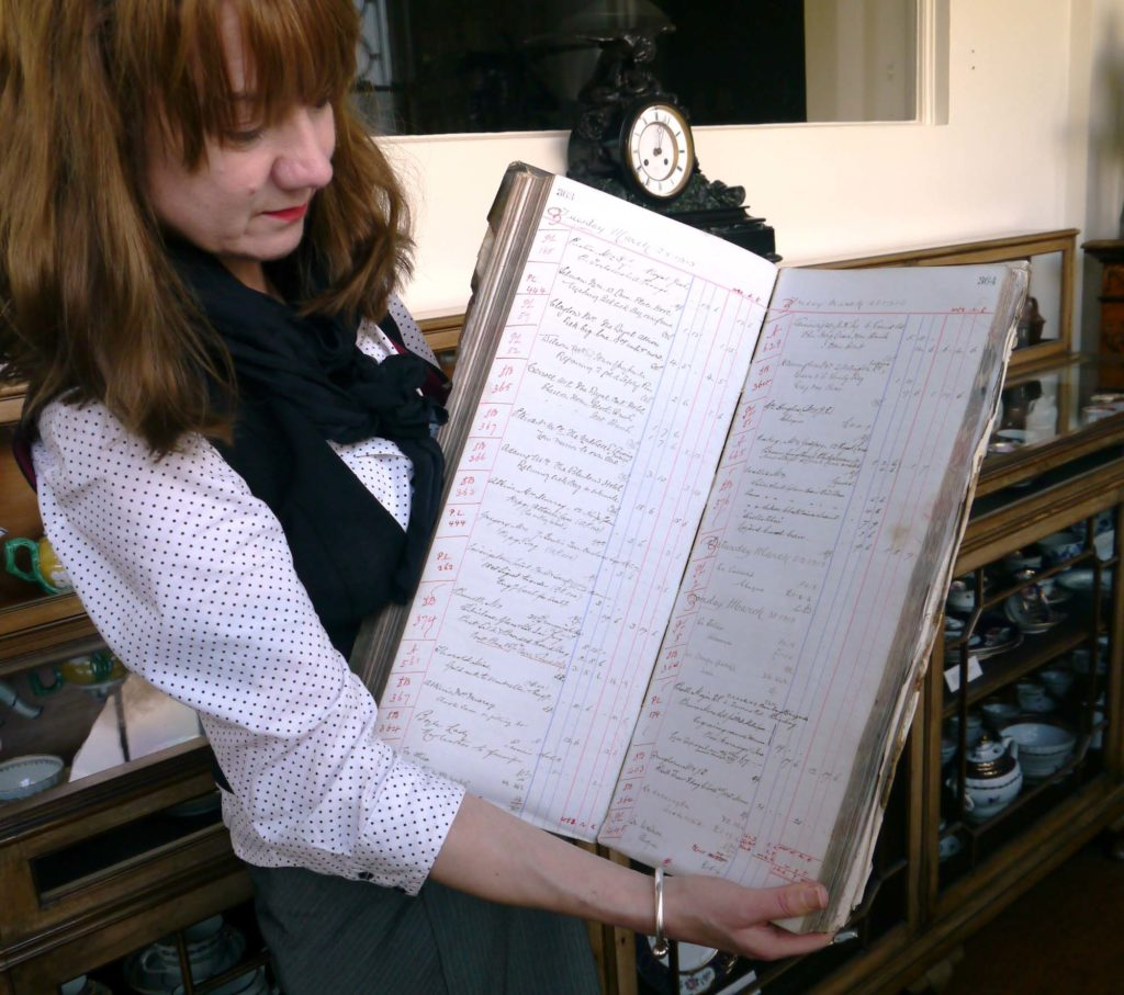a photo of a woman holding a large open book