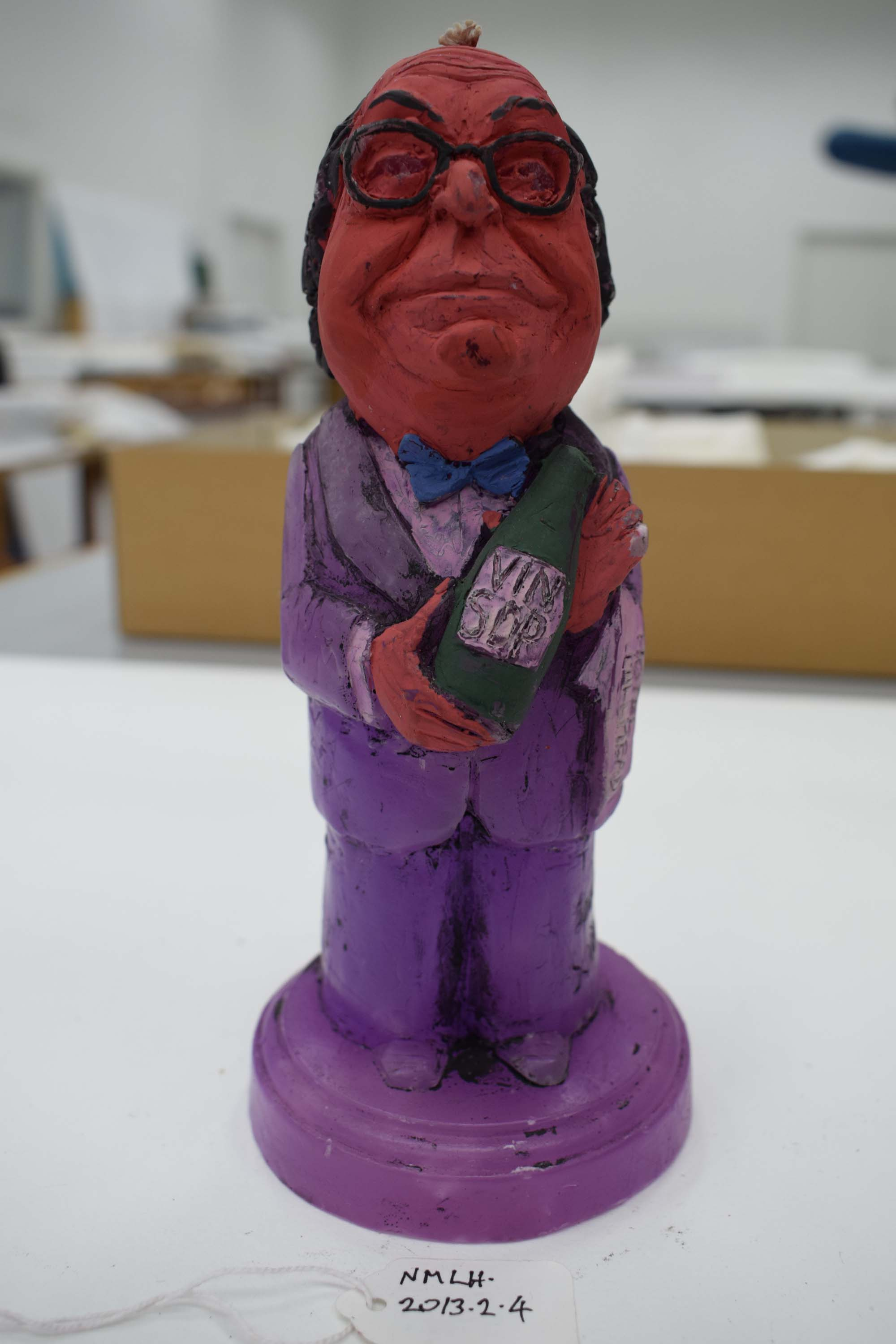 a photo of a wax candle of a politician holding a bottle of wine