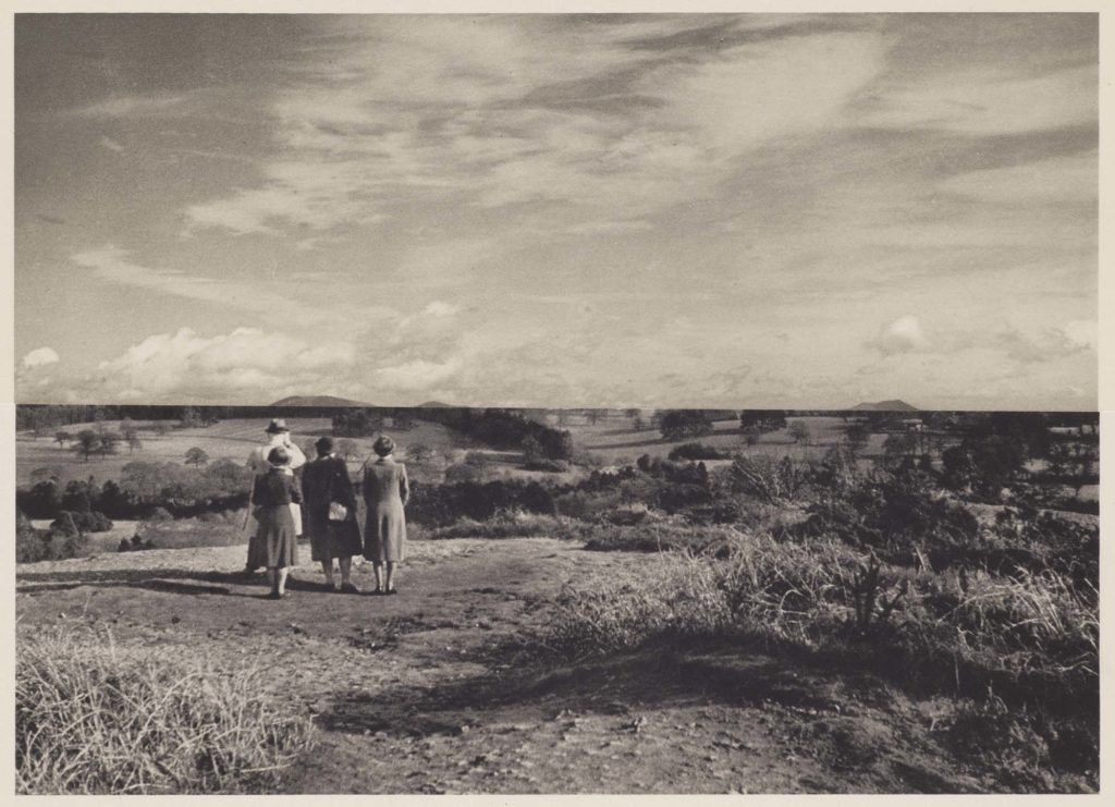 a montage photo of three people looking across a landscape with a sky superimposed across the top