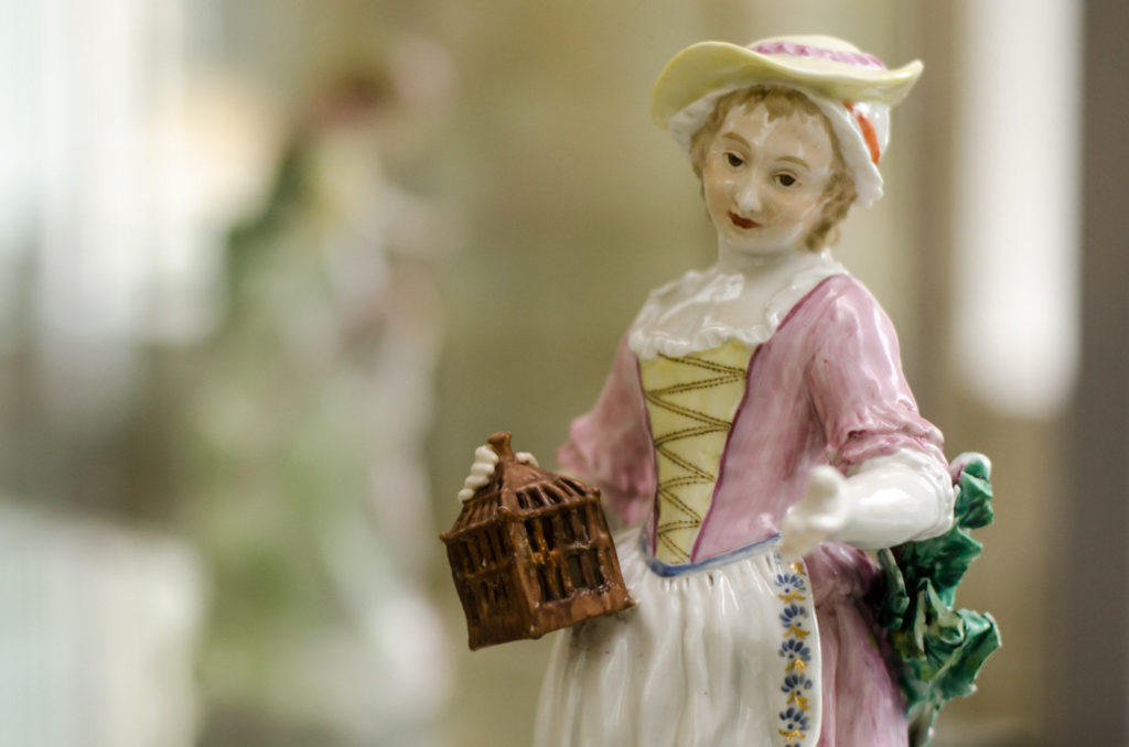 close up photograph of ceramic ornament figure of woman in pink and white