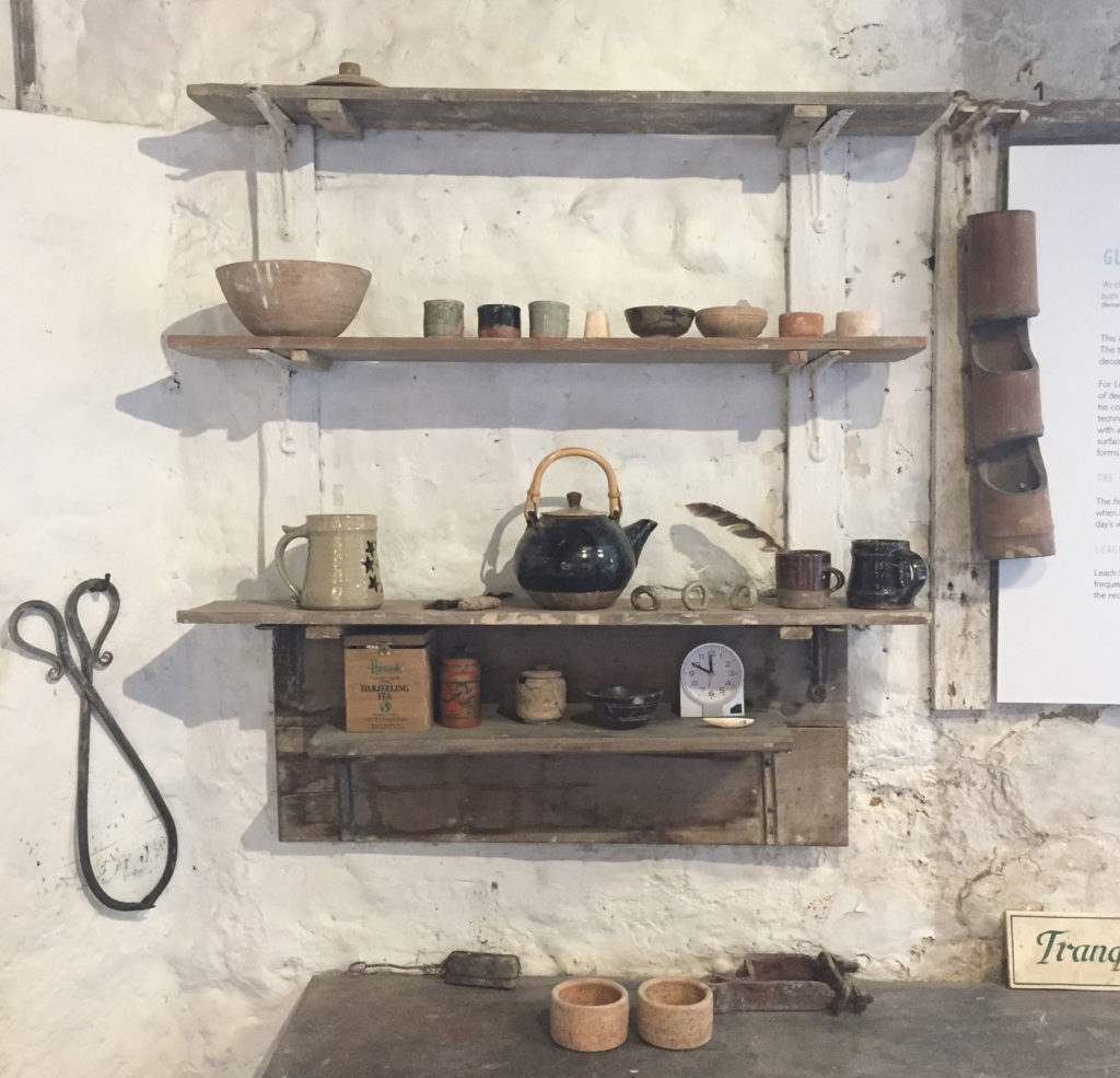 photograph of shelf in old pottery studio containing teapot, mugs and bowls