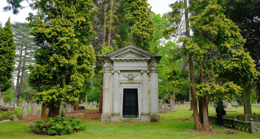 photograph of mausoleum within tree-filled cemetery
