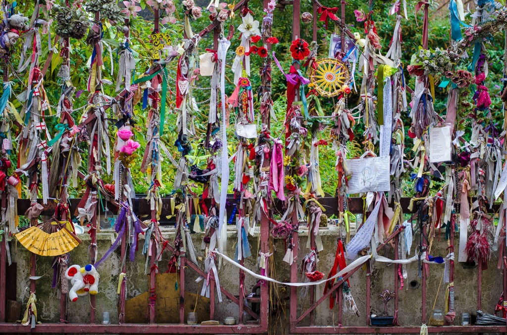 photograph of graveyard gates covered in colourful ribbons and trinkets