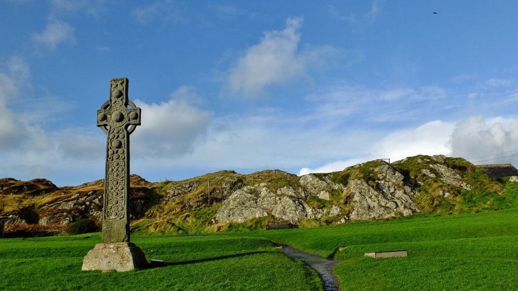 photograph of ancient cross monument in rocky landscape