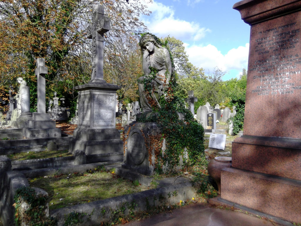 photograph of cross and angel monuments in cemetery