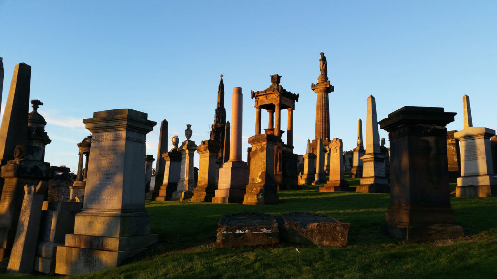 photograph of monuments in cemetery at sunset