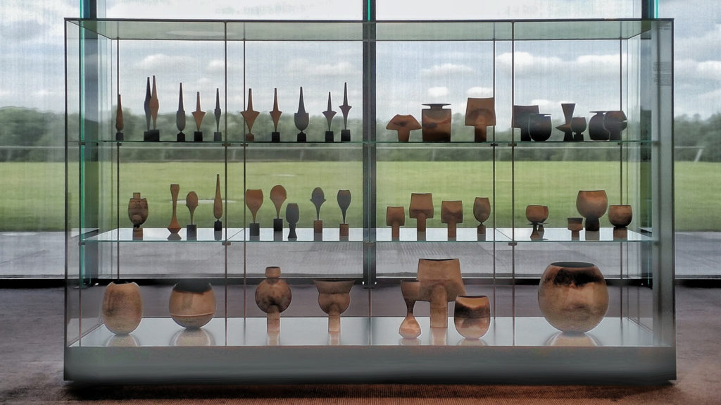 photogrpah of modern ceramic pots in large glass cabinet overlooking parkland