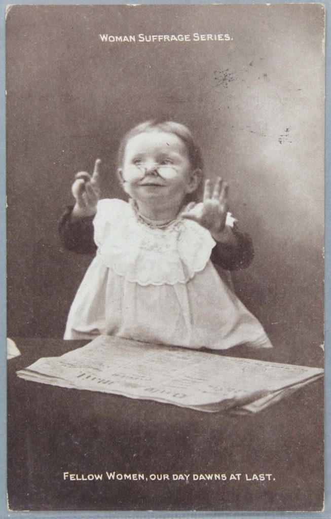 a pro suffragette postcard with a young girl wearing glasses standing in front of a newspaper with her hands raised and the caption reads 'Fellow women, our day dawns at last'.