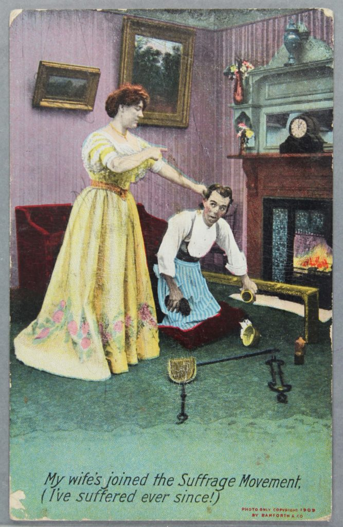 an ant suffragette postcard showing a woman holding a mans ear as he does the housework