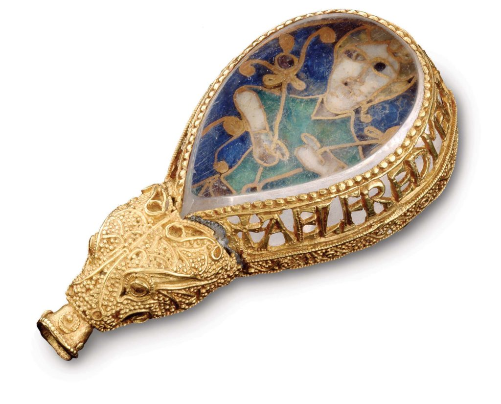 a photo of a gold jewel like ornament with a medieval styled portrait of a man inside it