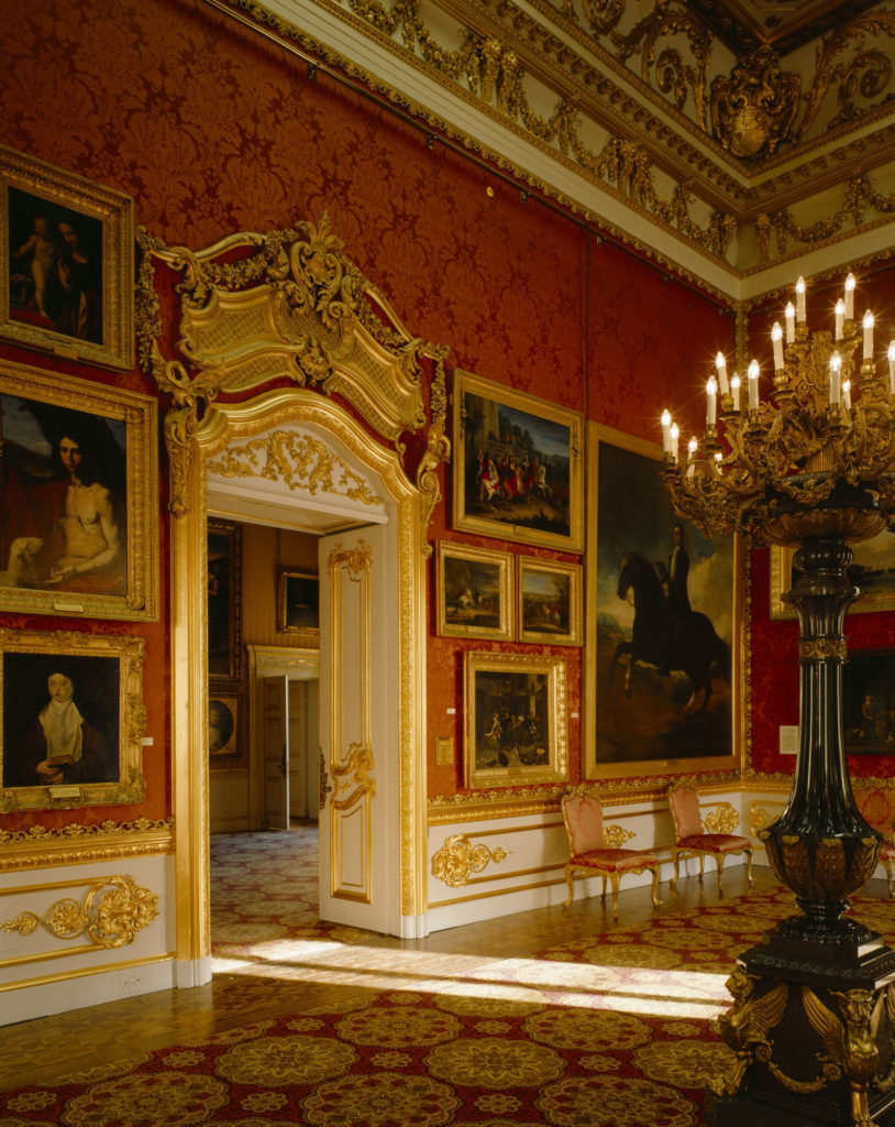 photograph of interior of lavishly decorated room with red wallpaper and paintings in gilded frames