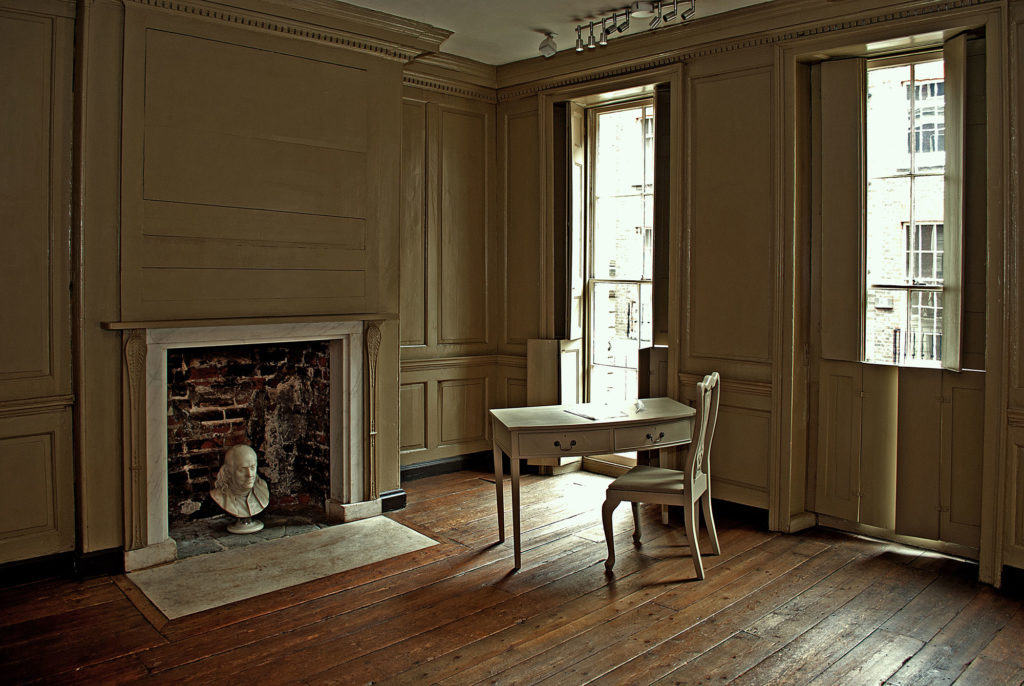 photograph of interior of regency building showing bust of man in fireplace and table with chair