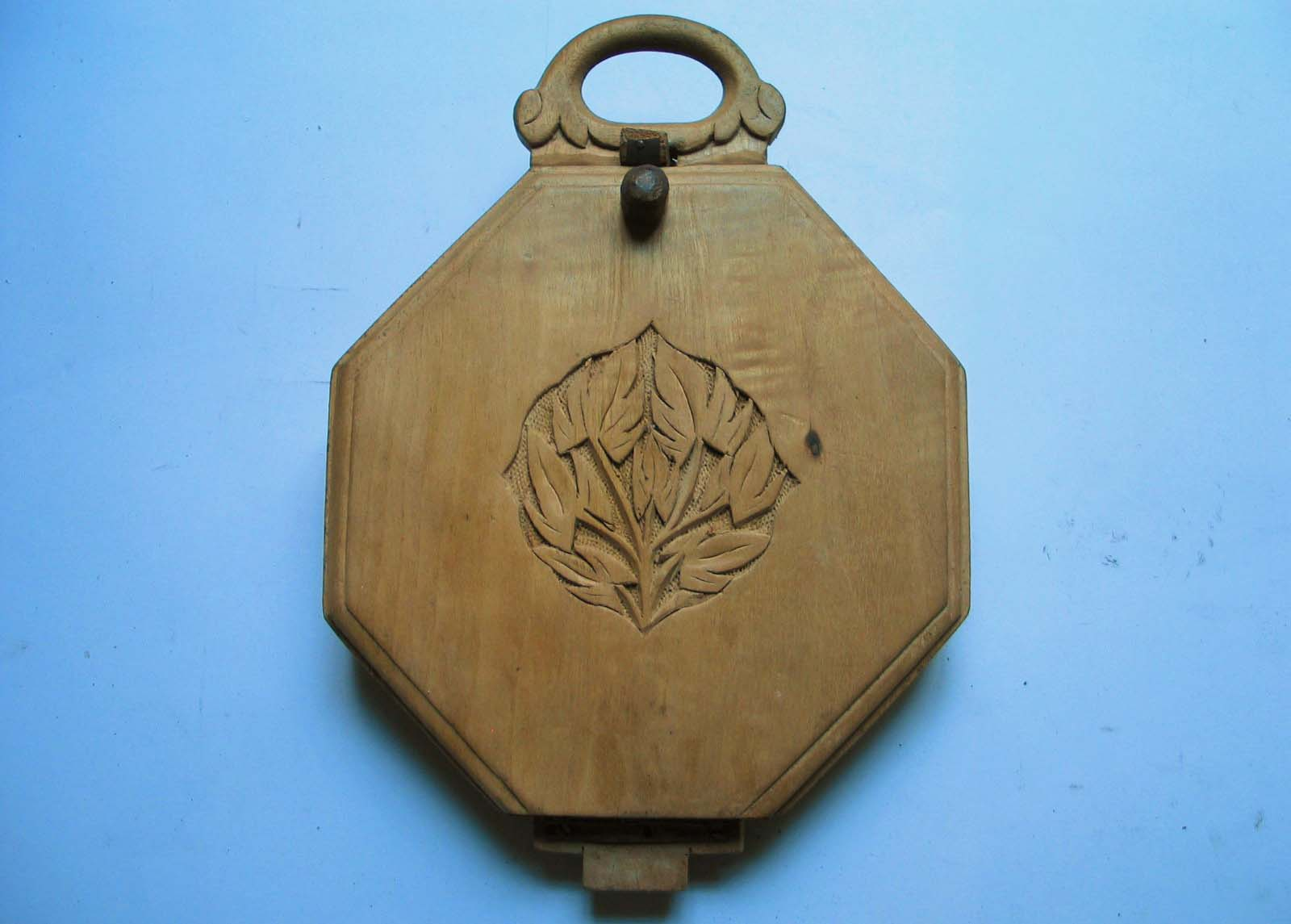 a photo of a carved wooden platfrom with a hing at at its top and flowers in its centre