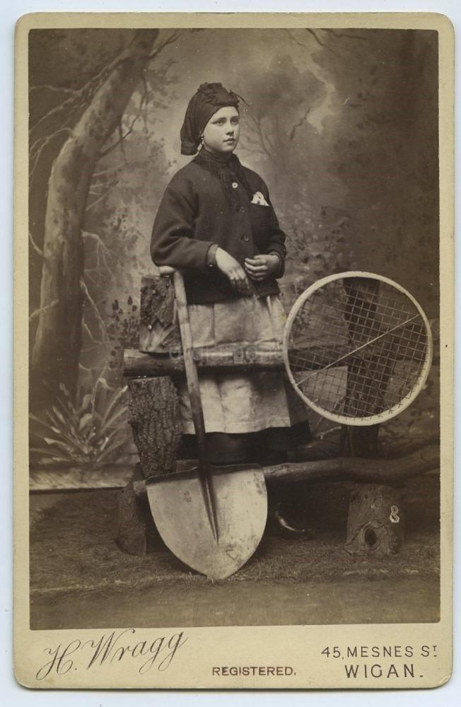 a blac and white photo of a woman wearing work clothes with a coal sieve and shovel