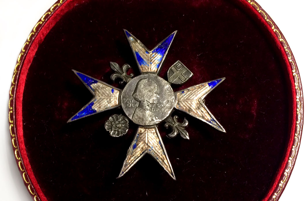 a photo of a medal in a Maltese Cross style with a woman's image in profile at its centre