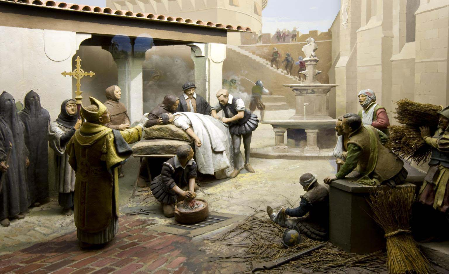 a model showing a medieval courtyard with a surgeon operating on a prone figure surrounded by medieval churchmen and other figures