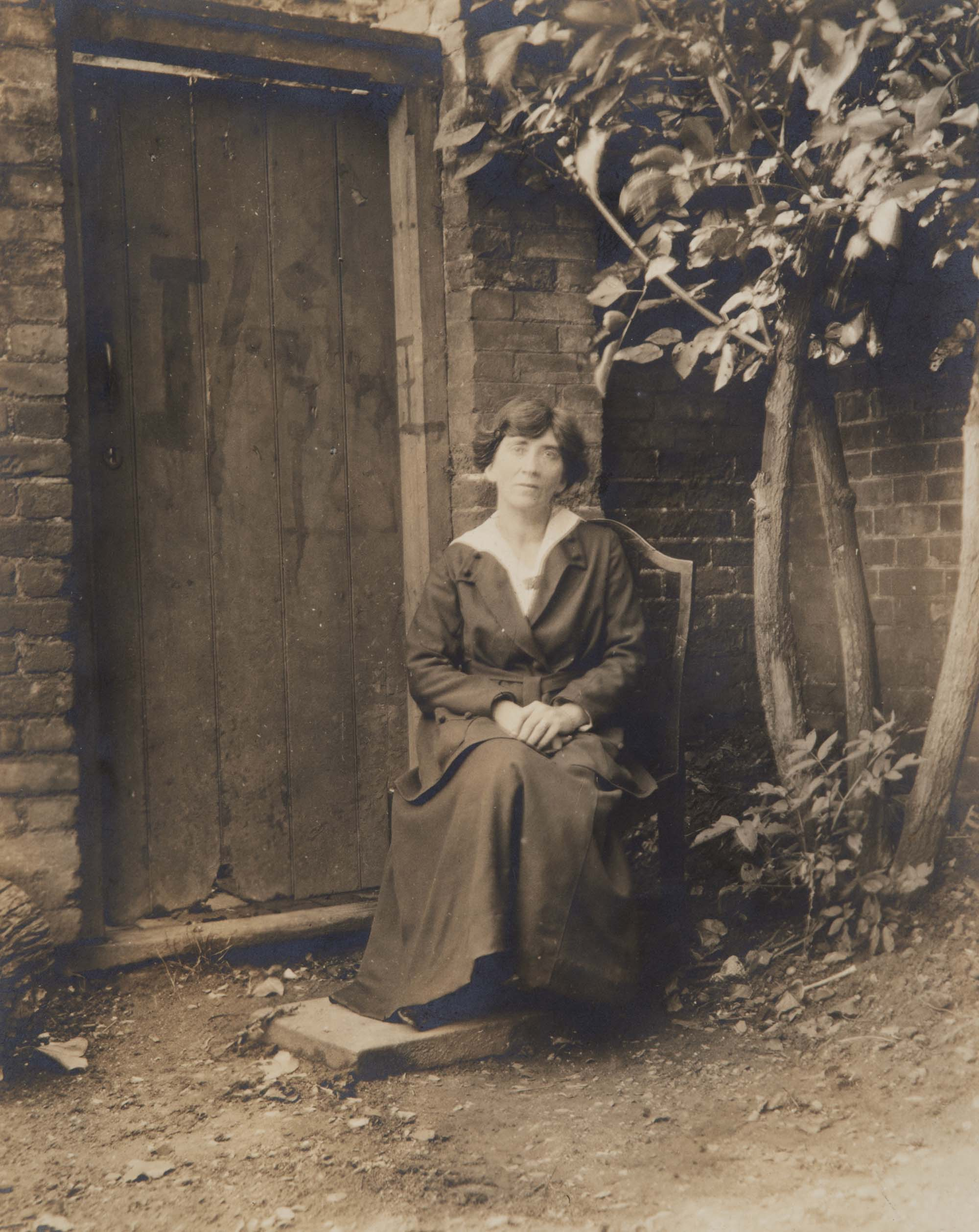 a photo of a woman in edwardian dress seated before a garden door