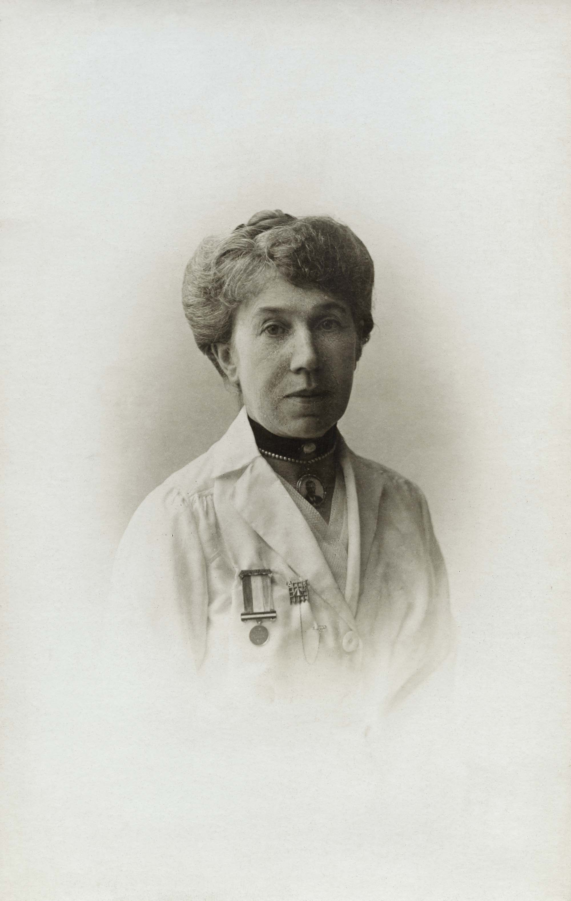 a portriat photographic postcard of a woman wearing a medal