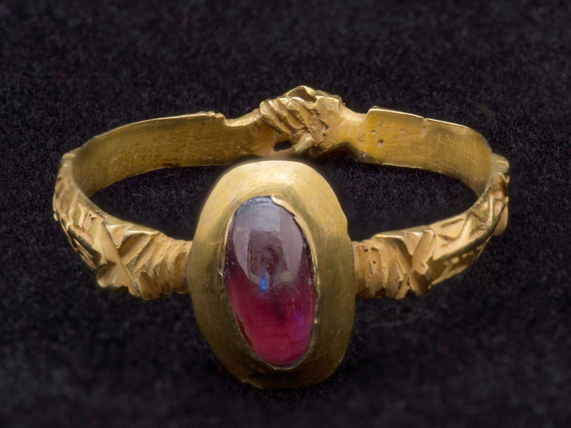 a golden ring with handclasp design on the band and a ruby stone