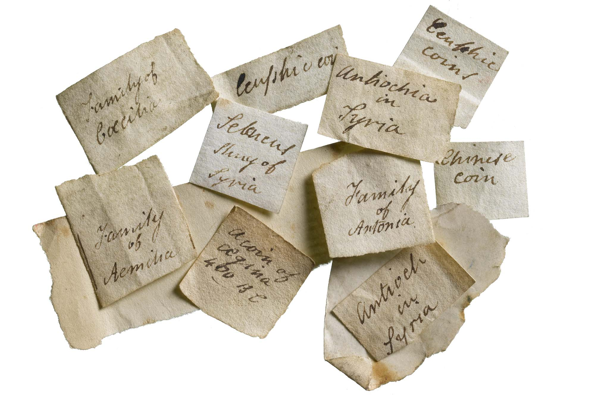 a photo of a group of small pieces of paper with handwriting on them