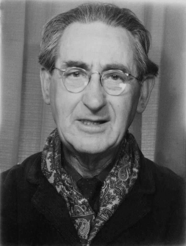 a passport booth photo of a middle aged man in scarf and glasses