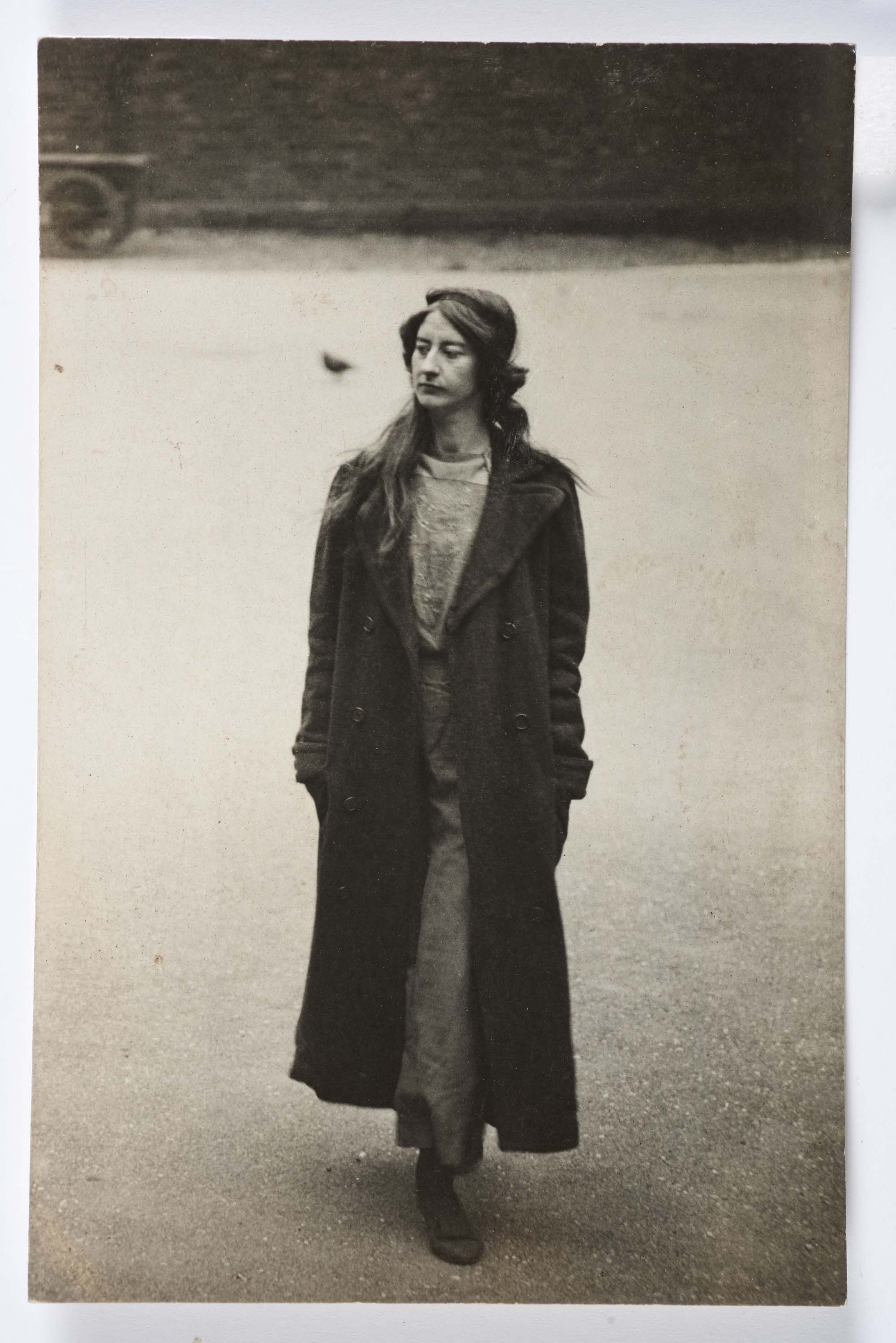 a blck and white photo of woman woth long haor and a long coat over overalls walking in a yard
