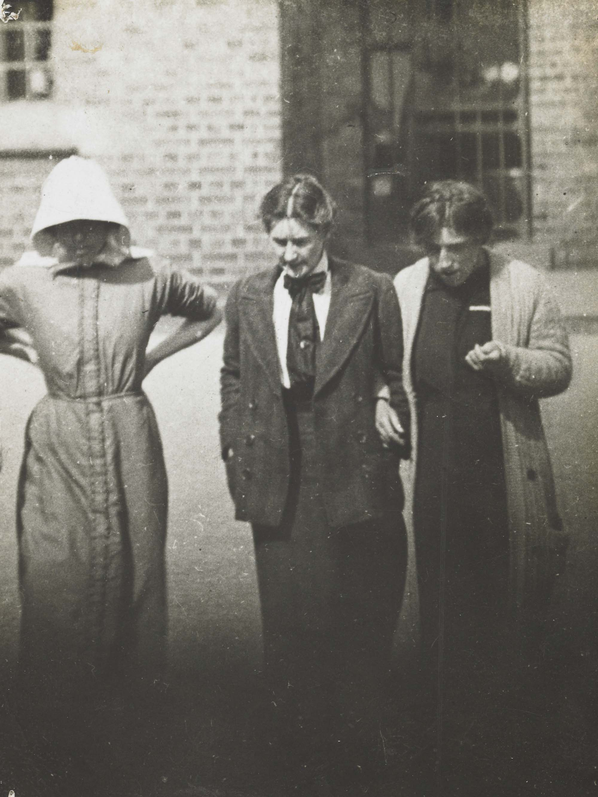 a photograph of three women in Edwardian dress walking across a yard