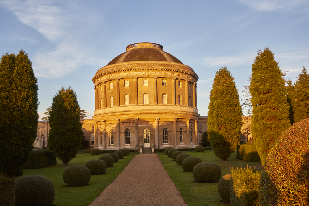 photograph of large rotunda building at the end of a tree-lined path