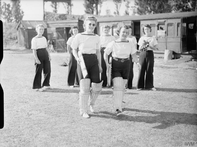 a phot of two women walking out to the crease