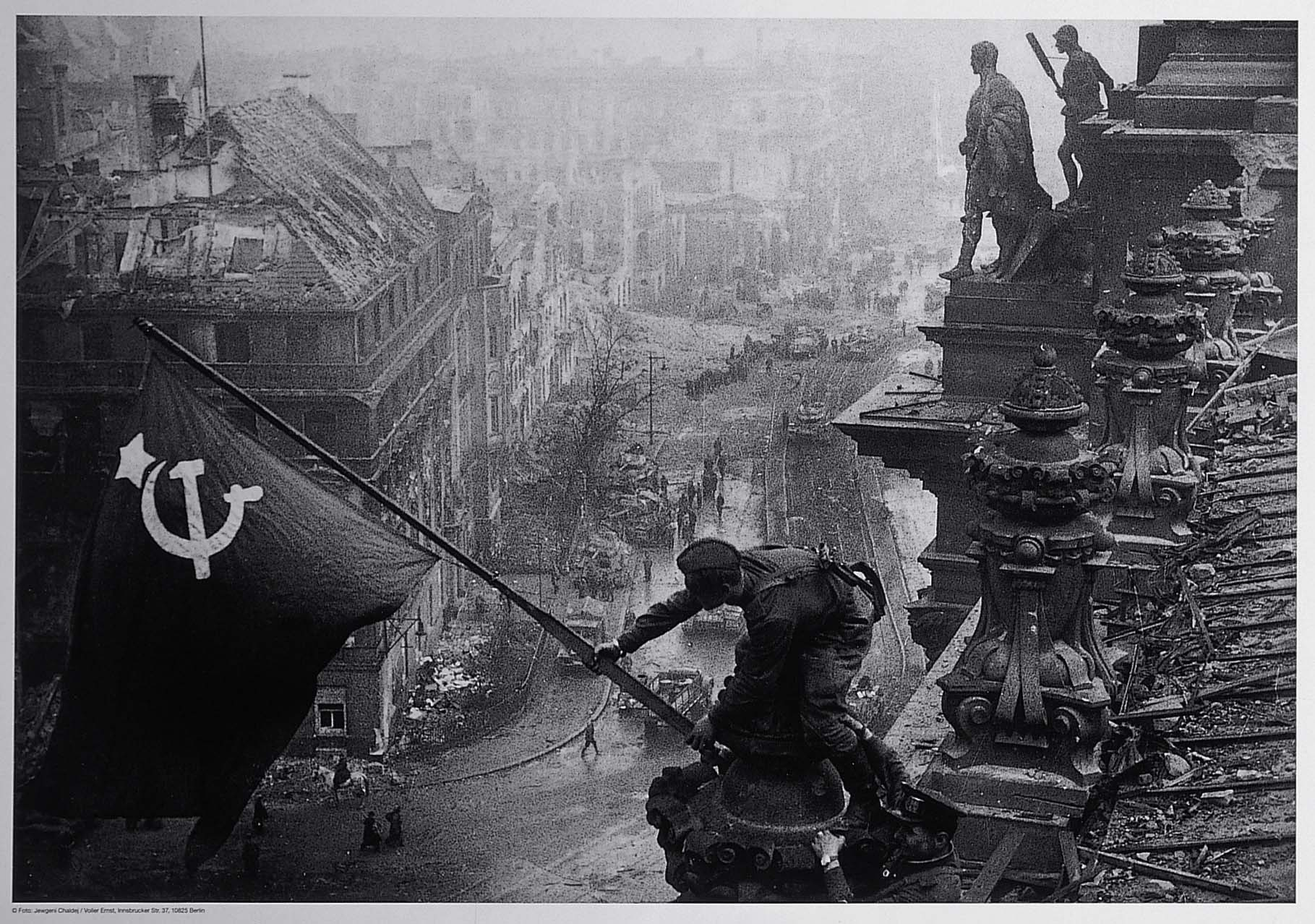 a photo of a soldier reaching over the ruined colonnade of a shattered building in Berlin to raise a red flag above streets with tanks and soldiers visible amidst the debris and burnt out buildings