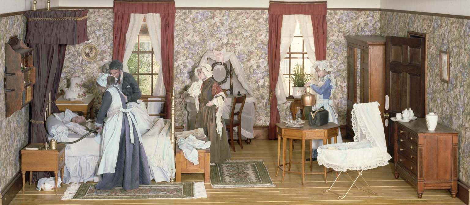 a model of Victorian bedroom with a womna on the bed attended by a doctor and nurse