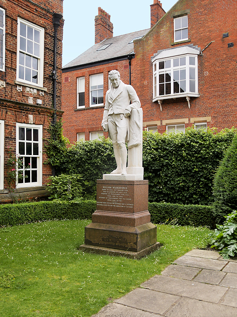 photograph of statue of man leaning against post outside a large red brick house
