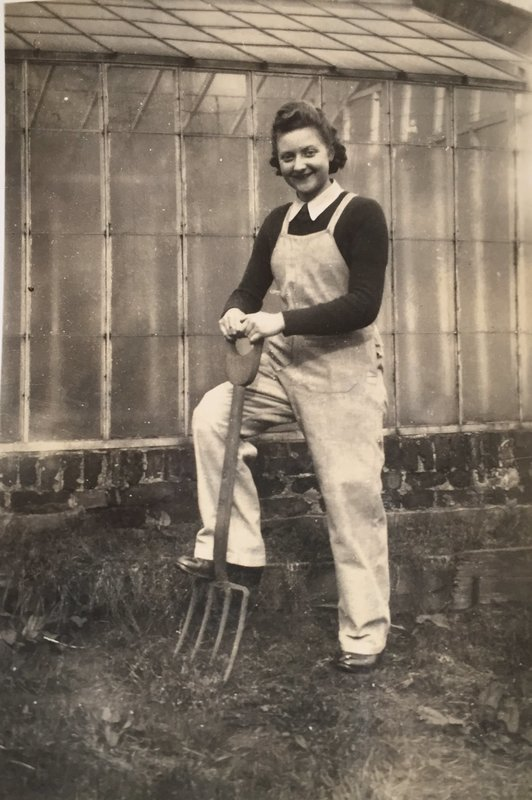 a photo of a woman in overalls leaning on a spade