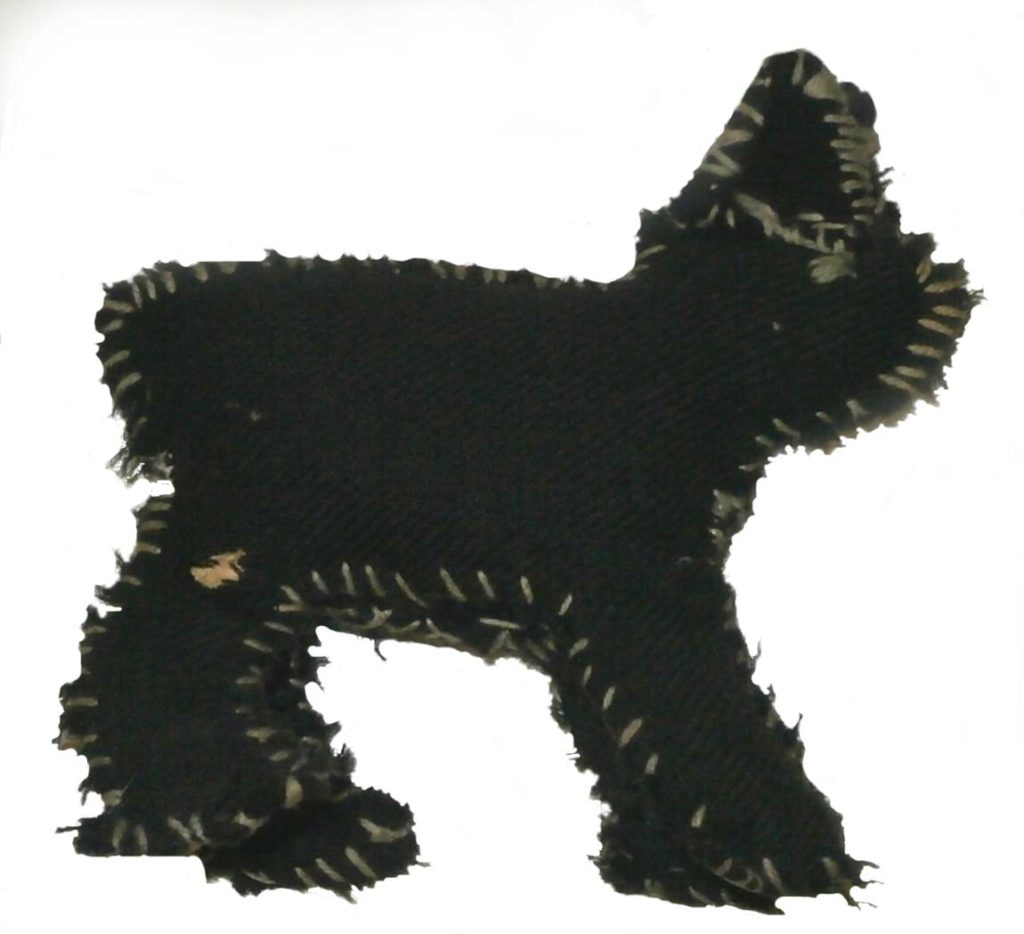 a photo of a roug made toy cat out of black fabric