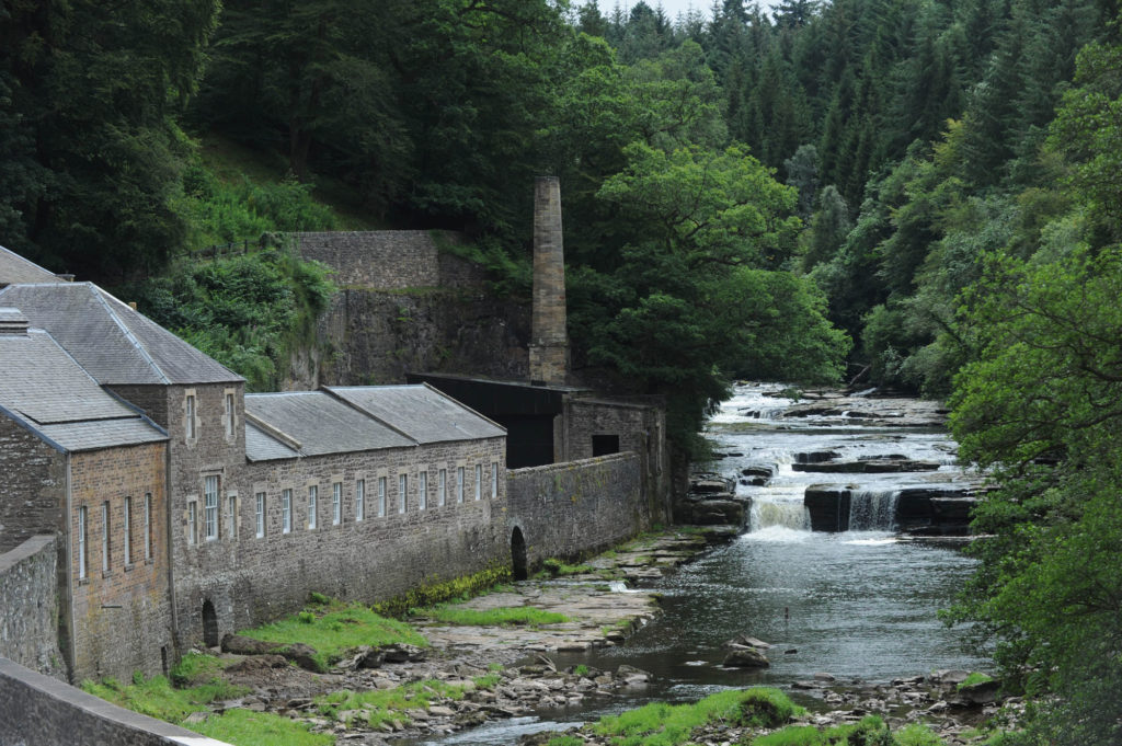 photograph of industrial buildings lining river with falls, large trees in background